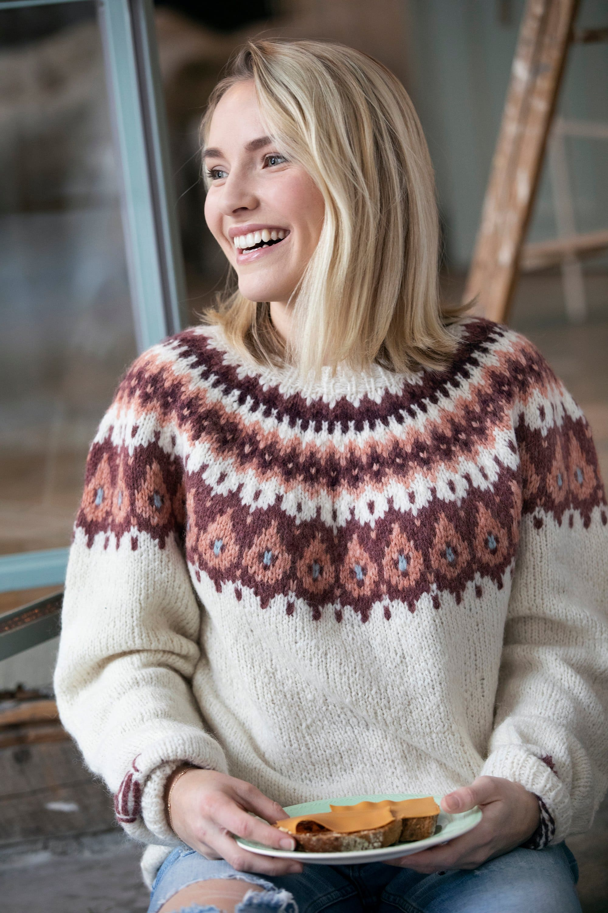 Girl smiling while wearing the Brunost sweater